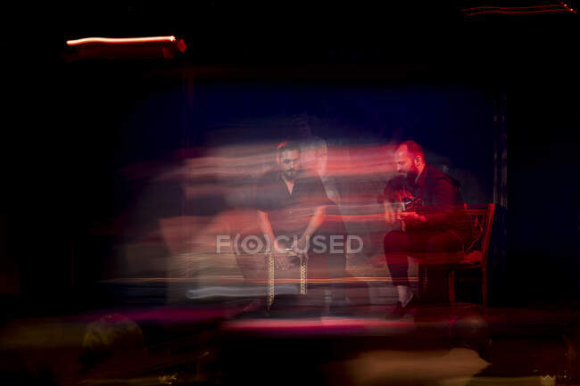 Hispanic men playing percussion and acoustic guitar during flamenco performance on dark stage — Stock Photo