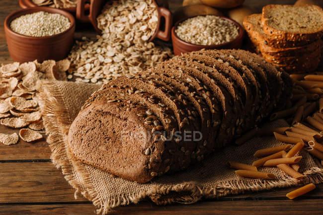 Freshly baked sliced rye bread on napkin on wooden table — Stock Photo
