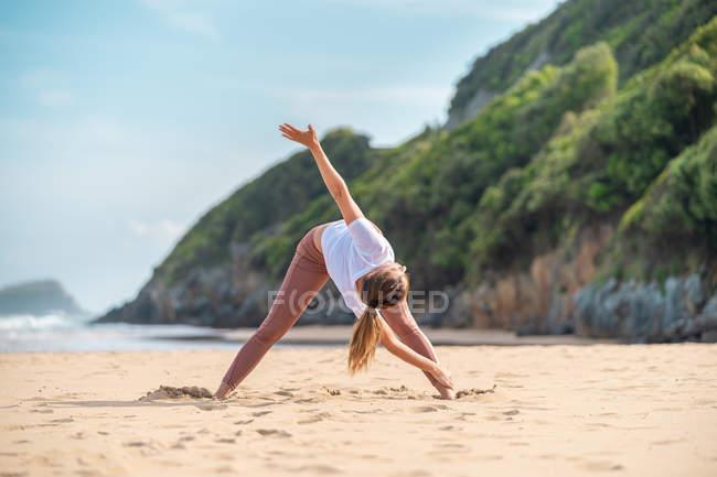 Маленькая стройная женщина, тренирующаяся на берегу моря — стоковое фото