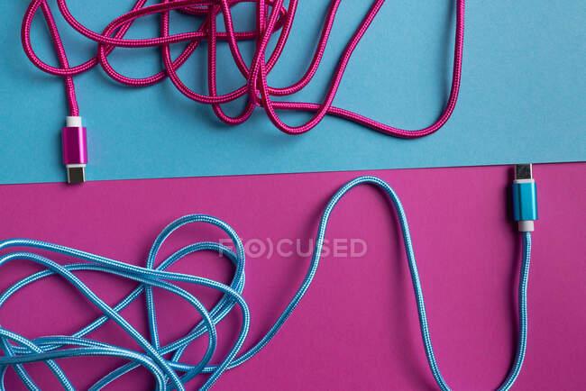 Vista superior de cables USB de color rosa y azul sobre fondo de cartón colorido - foto de stock