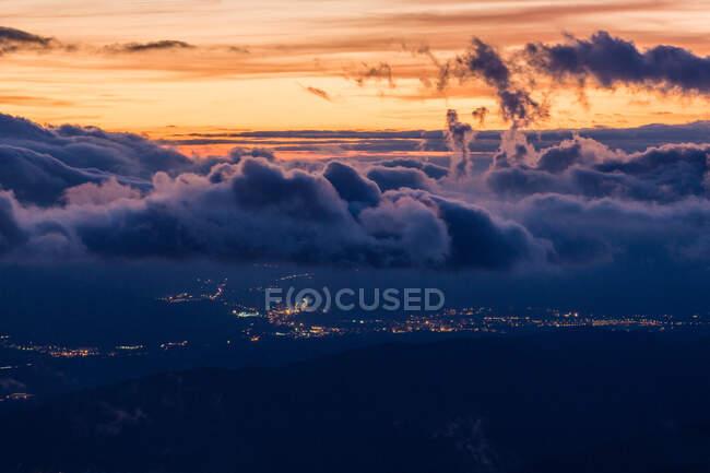 Paysage des lumières brumeuses de la ville éloignée dans le terrain sous les nuages sombres pelucheux avec le ciel couchant — Photo de stock