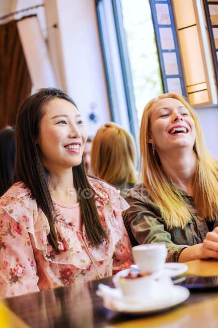 Молодые многорасовые женщины улыбаются и разговаривают друг с другом, сидя за столом в уютном кафе — стоковое фото