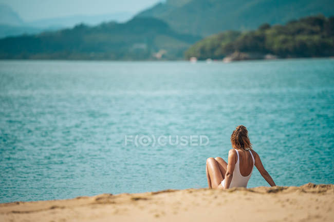 Woman in swimsuit sitting on sandy beach and looking at view — Stock Photo