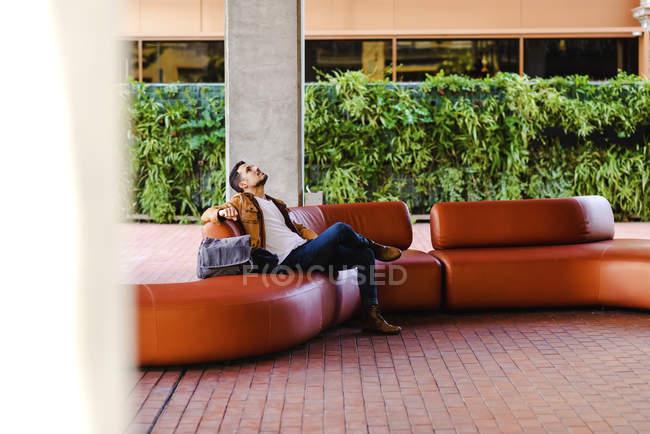 Mann im schicken Outfit sitzt auf bequemer roter Ledercouch in modernem Gebäude — Stockfoto