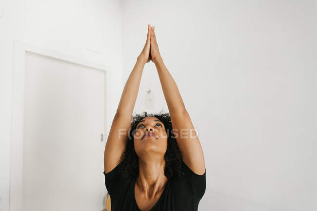 African American woman performing yoga posture with stretched arms in light room — Stock Photo