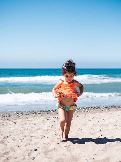 Back view of little sisters in bright orange dresses walking together on seaside in sunny day — Stock Photo