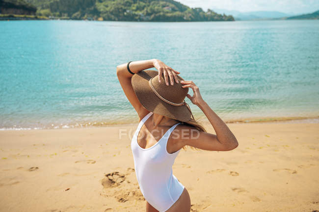Woman in hat and swimsuit posing on sandy beach — Stock Photo