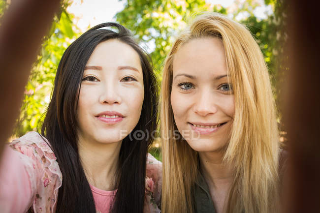 Multiethnic young women smiling and looking at camera while taking selfie against green trees in park — Stock Photo