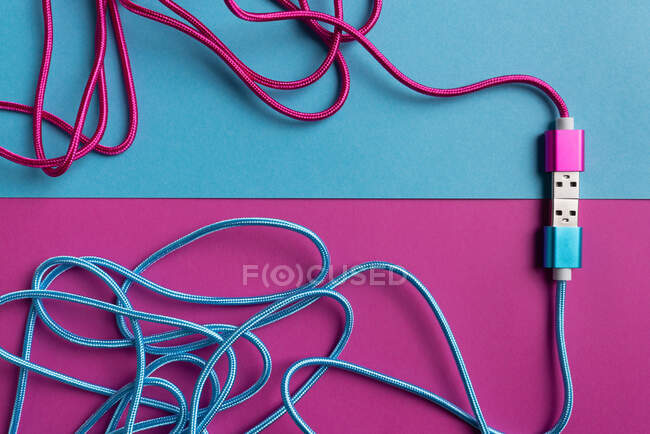 Top view of neon pink and blue colored USB cables on colorful cardboard background — Stock Photo