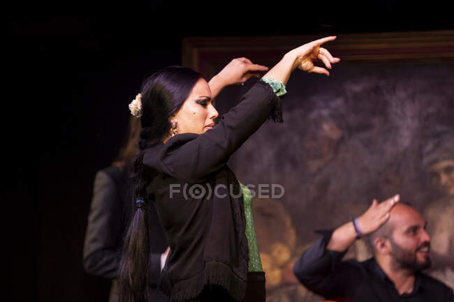 Woman in black costume dancing flamenco near Hispanic male musicians during performance against painting on dark stage — Stock Photo