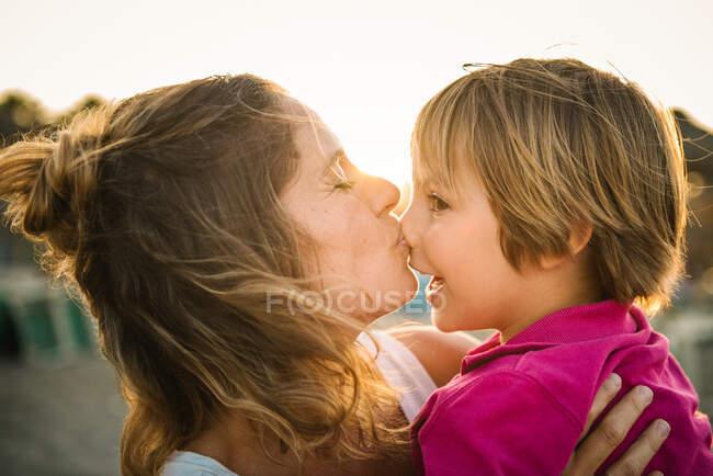 Vista lateral de la mujer riendo llevando alegre hijo juguetón en las manos mientras besa su nariz en la playa al atardecer - foto de stock