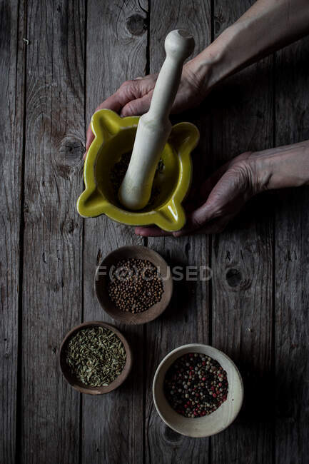Crop view from above of cook grounding spices in mortar while cooking at wooden table — Stock Photo
