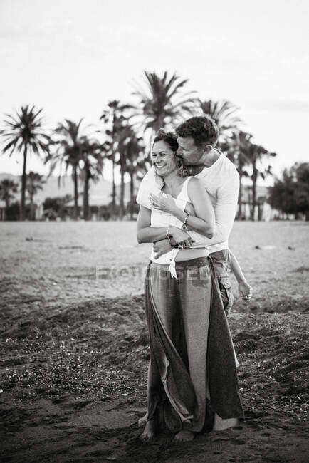 Чорно-білий дорослий чоловік і жінка обіймають і цілуються на пляжі. — стокове фото