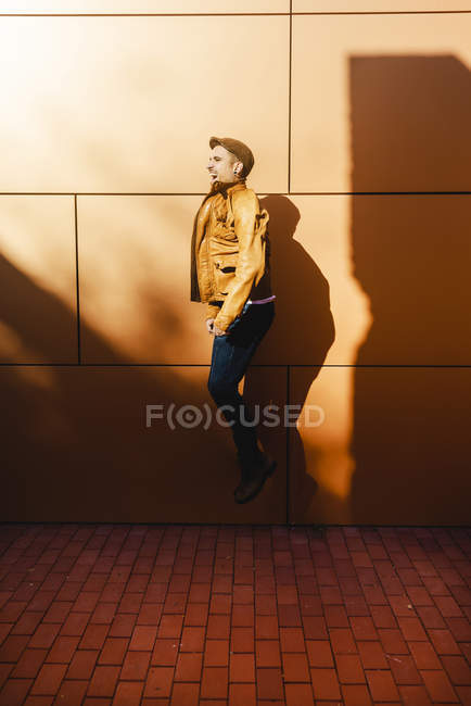Positive young man in stylish outfit jumping near wall of modern building on sunny day — Stock Photo