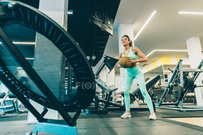 Young athletic woman in sportswear training with ball in gym — Stock Photo