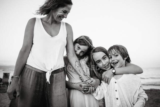 Чорно-білий дорослої сміється жінка з прекрасними дочками і сином обіймаються на пляжі — стокове фото