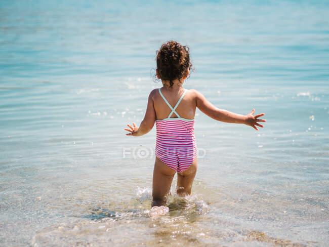 Visão traseira da menina bonito alegre anônimo jogando na água do mar no fundo da costa calma — Fotografia de Stock