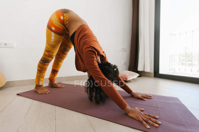 Woman performing yoga pose with head down and stretching on mat in light room — Stock Photo
