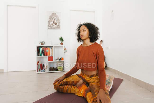 Афроамериканская молодая женщина, исполняющая позу йоги со скрещенными ногами и медитирующая с закрытыми глазами дома — стоковое фото