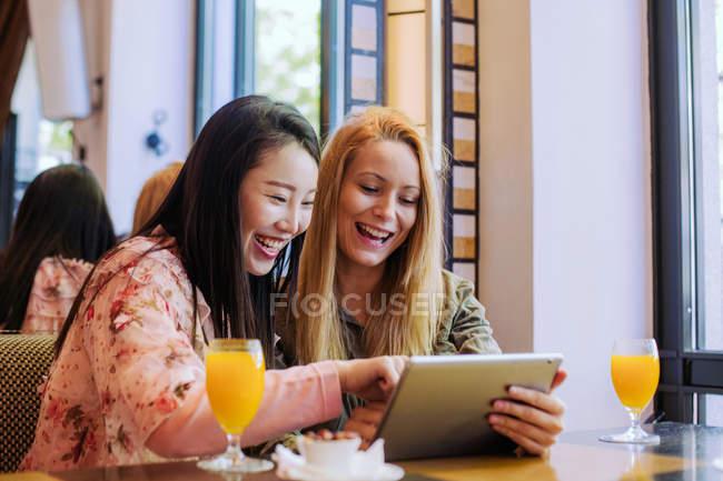 Mulher branca jovem mostrando vídeo no tablet para surpreendido amigo asiático enquanto sentado na mesa de café juntos — Fotografia de Stock