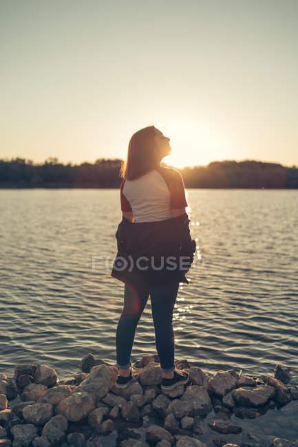 Donna in piedi vicino al lago al tramonto — Foto stock