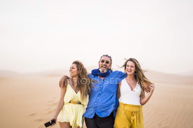 Homme barbu senior riant et embrassant les femmes gaies tout en marchant dans le désert sablonneux pendant le voyage au Maroc — Photo de stock