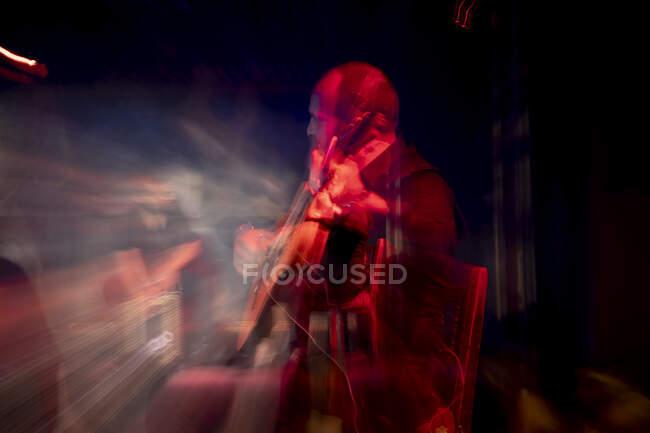 Hombre hispano tocando la guitarra acústica durante la actuación flamenca en el escenario oscuro - foto de stock