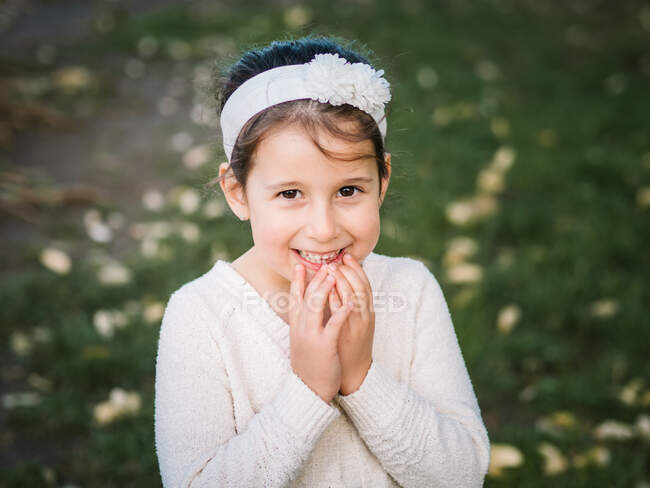 Ritratto di adorabile ragazza felice guardando la macchina fotografica sullo sfondo del parco estivo — Foto stock