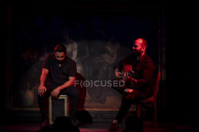 Uomini ispanici che suonano percussioni e chitarra acustica durante le esibizioni di flamenco sul palco buio — Foto stock