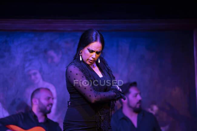 Жінка в чорному вбранні танцює фламенко біля латиноамериканських музикантів під час виступу проти малювання на темній сцені. — стокове фото