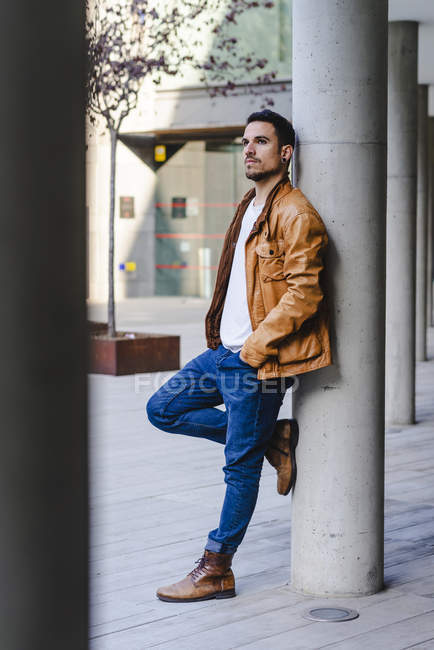 Confident trendy young guy leaning on concrete pillar outside contemporary building on city street — Foto stock