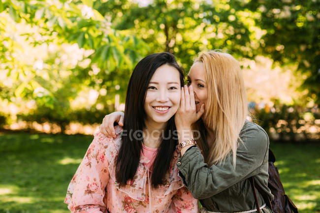 Young Caucasian woman smiling and whispering secret into ear of smiling Asian friend while spending time in park together — Stock Photo