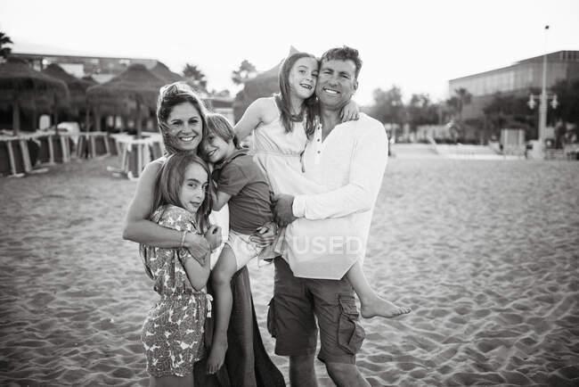Дорослі чоловіки і жінки з сином і дочками стоять разом на пляжі і посміхаються в камері чорно-білої фотографії. — стокове фото