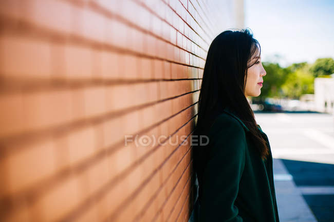 Pensive Asian woman in trendy outfit and looking away while leaning on brick wall — Stock Photo