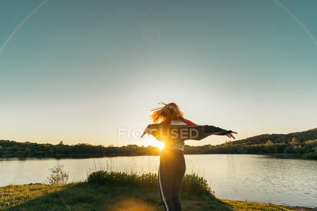 Femme debout près du lac au coucher du soleil — Photo de stock