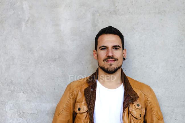 Confiante na moda cara jovem inclinado na parede de concreto — Fotografia de Stock