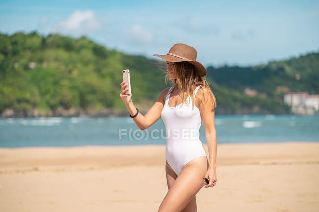 Smiling young woman in swimsuit and hat using smartphone on beach — Stock Photo