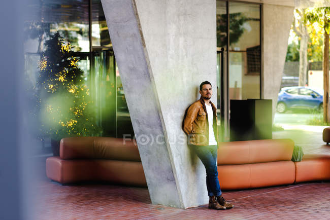 Confident trendy guy leaning on concrete pillar near leather couch outside contemporary building on city street — Foto stock
