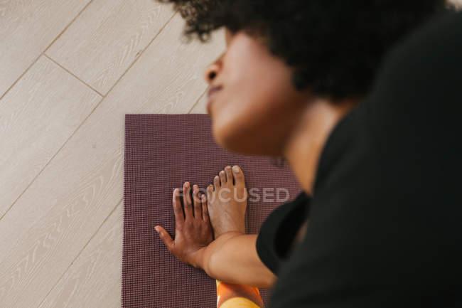 Closeup of woman performing yoga pose on a mat at home - foto de stock