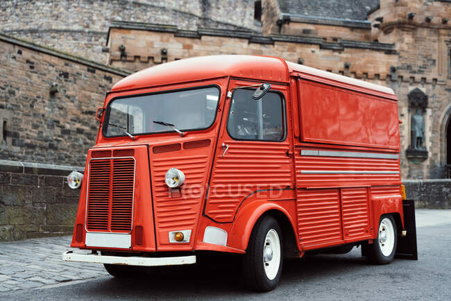 Retro red colored van on roadside with aged stone castle on background, Scotland — Stock Photo