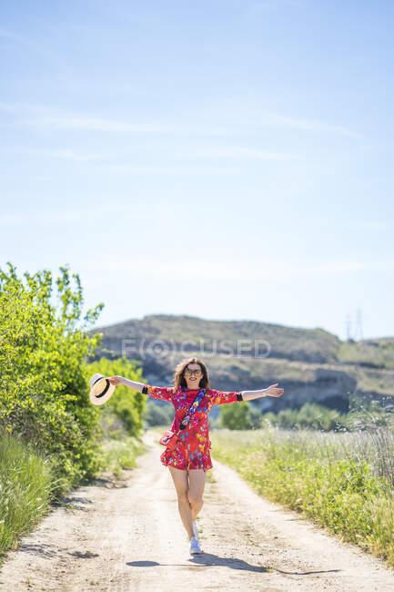 Jeune femme excitée en tenue tendance étirant les bras et souriant tout en marchant le long de la route de campagne par une journée d'été ensoleillée — Photo de stock