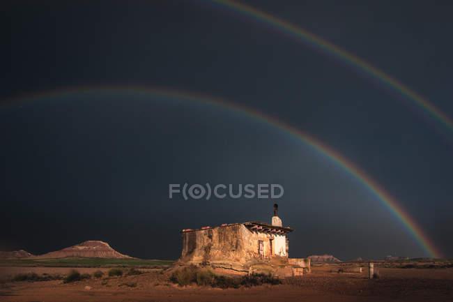 Casa velha só no deserto e no arco-íris no céu tormentoso — Fotografia de Stock