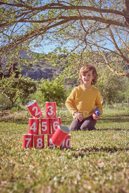 Allegro bambino inginocchiato e lanciare palle in piramide di lattine rosse sullo sfondo della natura — Foto stock