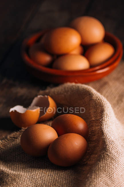 Chicken eggs and eggshell with bowl and sackcloth on wooden table — Stock Photo