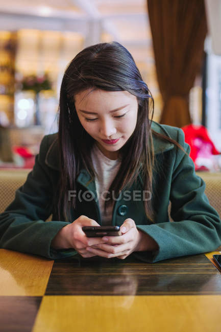 Beautiful Asian woman browsing modern smartphone while sitting at table in cozy cafe — Stock Photo