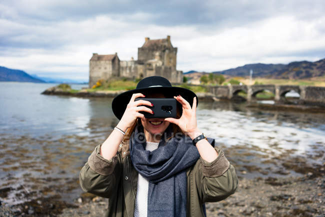 Cheerful stylish woman using phone taking photo against old stone castle on coast in mountains, Scotland — Stock Photo