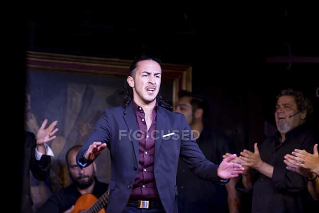 Hombre de traje azul bailando flamenco cerca de músicos masculinos hispanos durante la actuación contra la pintura en el escenario oscuro - foto de stock