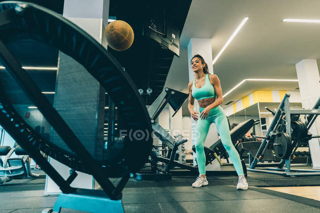 Young athletic woman in sportswear training with heavy ball in gym — Stock Photo