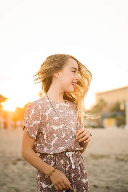 Menina sorridente em vestido e acessórios acenando com o cabelo em pé na praia ao pôr do sol luz — Fotografia de Stock