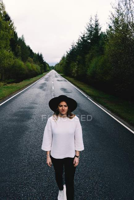 Trendy woman in black hat standing in solitude on remote road with lush green trees, Scotland — Stock Photo